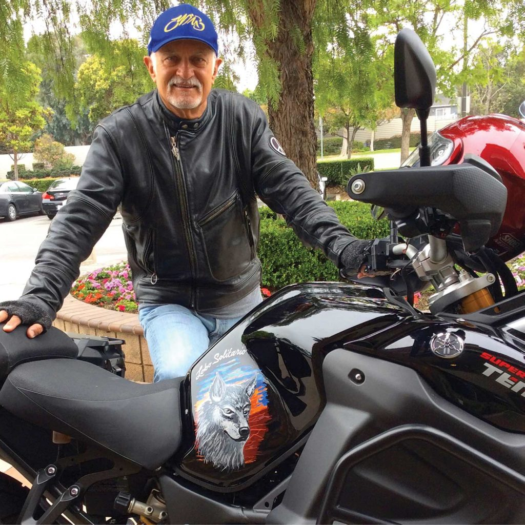 Mark Fargo, an older light-skinned man with white hair and goatee, stands in a leather jackety behind a black motorcycle with a wolf painted on it.